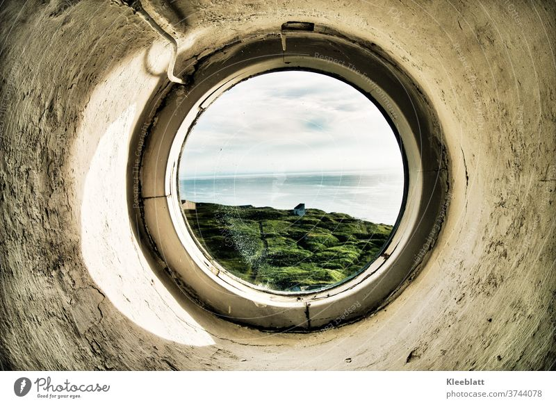 Durch ein rundes Bullauge des Leuchtturms den Blick auf's Meer gerichtet rundes Fenster grob verputzte Wand grau-weiße Farbe altes Fenter Blick aufs Meer