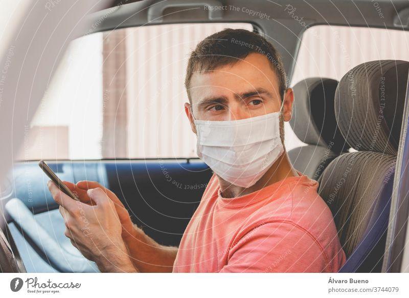 Ein junger Mann, der einen Mundschutz aus Stoff trägt, überprüft das Mobiltelefon im Auto Menschen schützend Virus Pflege Erwachsener Person Porträt Schutz