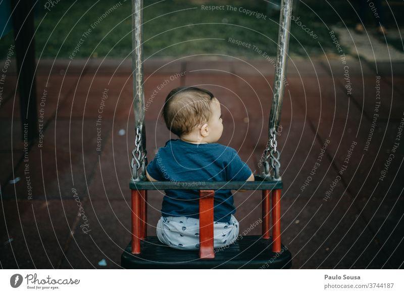 Rückansicht Kind spielt auf der Schaukel pendeln Spielplatz Kinderspiel Kindheit authentisch Textfreiraum unten Kleinkind Freizeit & Hobby Tag Farbfoto