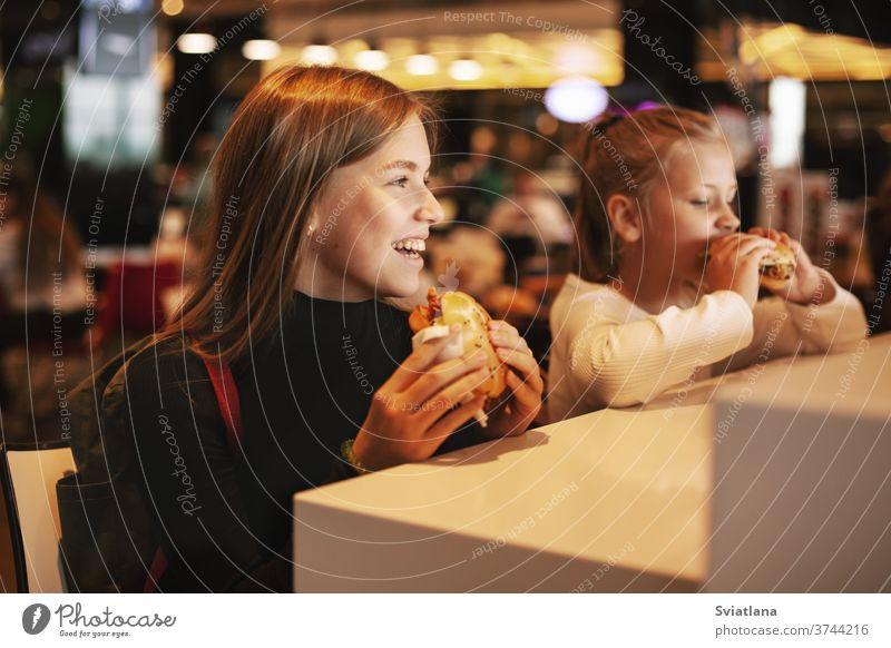 Hübsches Schulmädchen isst Hamburger und sitzt drinnen in einem Cafe. Glückliches Kind, das Junkfood in einem Restaurant isst. Seitenansicht Lebensmittel
