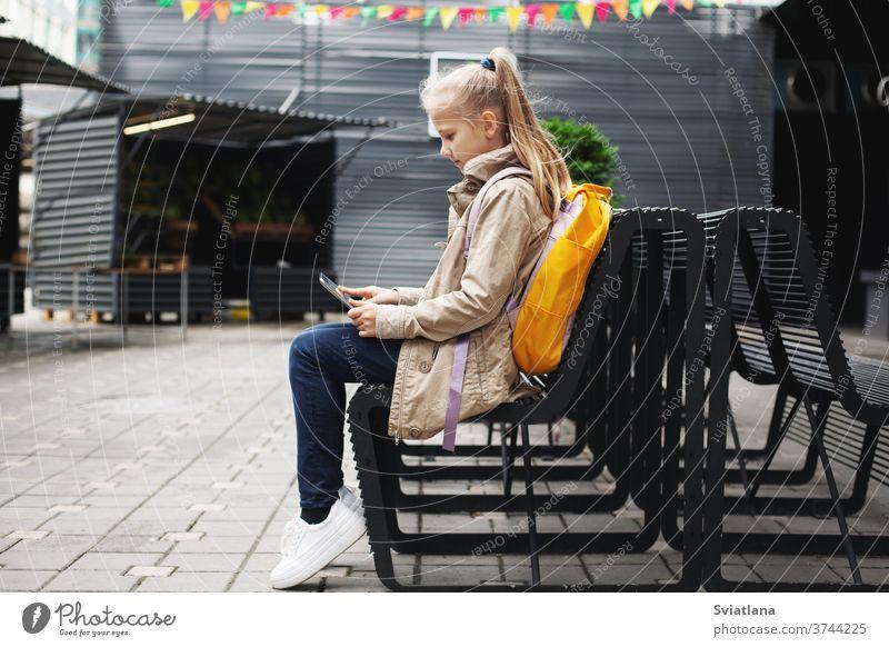Nach der Schule sitzt ein süßes Mädchen auf einer Bank und wartet auf den Bus, lernt online auf einem Tablett und kommuniziert per Video. Tablette Rucksack
