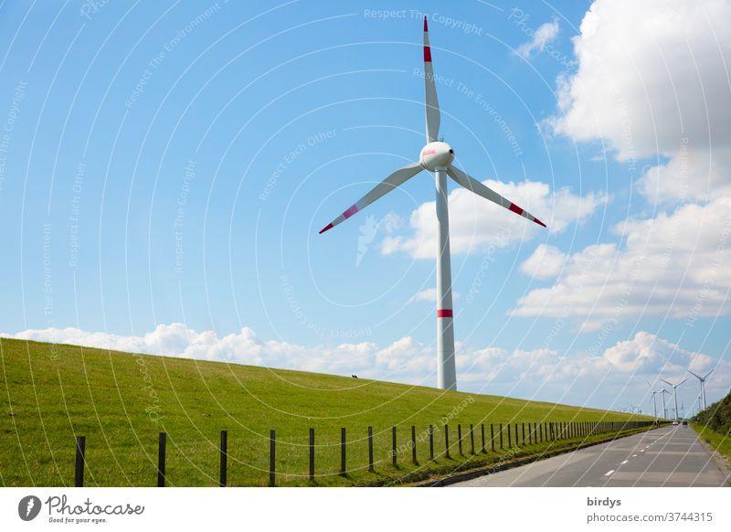 Windrad zur erneuerbaren Stromerzeugung vor einem Deich an der Nordseeküste, lange gerade Straße. Windkraftanlage Windenergie Erneuerbare Energie windräder