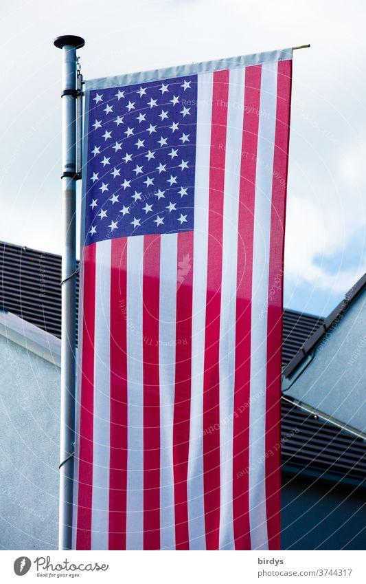 US-amerikanische Nationalflagge vor einem Gebäude. USA Flagge Fahne Amerika Stars and Stripes Fahnenmast formatfüllend Patriotismus Himmel Haus Streifen Sterne