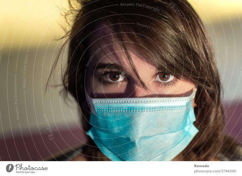 Nahaufnahme einer jungen Frau mit chirurgischer Maske und Blick in die Kamera. Person Mundschutz Korona starren Coronavirus Porträt Auge Gesicht tragend