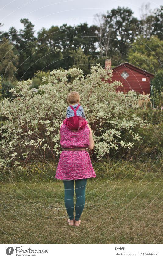 Huckepack mama huckepack pink Garten Kleingarten getragen getragen werden sitzen Kindheit Im Freien im Grünen Rücken Rückansicht Mama im Freien Zusammensein