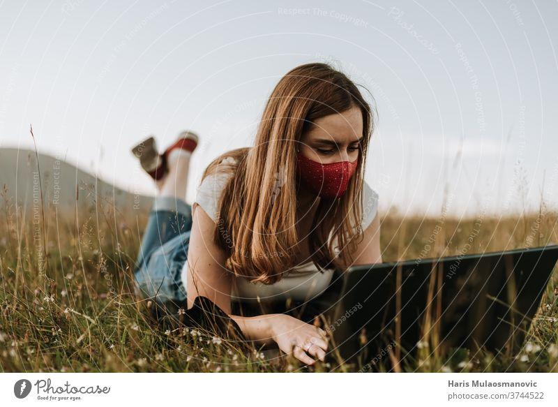 Frau mit Maske, die an einem Laptop im Freien arbeitet Erwachsener attraktiv schön Korona niedlich Tagesablauf Gesichtsmaske Mode Freiberufler Behaarung Glück
