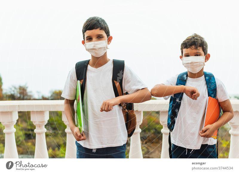 Anstoßen mit dem Ellbogen. Ellbogengruß zwischen Freunden zur Vermeidung der Verbreitung des Coronavirus (COVID-19). Keine Hände schütteln. Kind