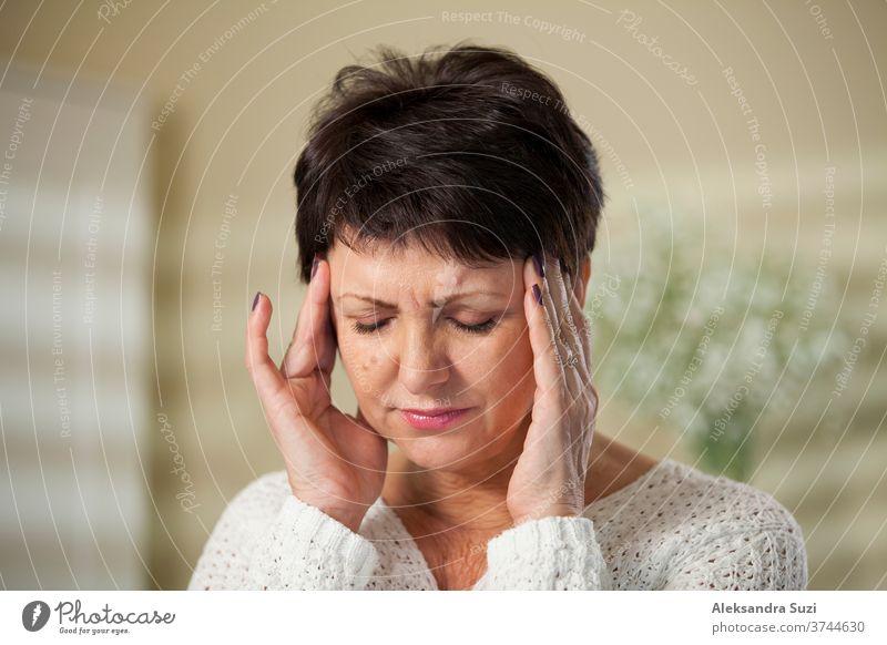 Attraktive reife Frau mit Kopfschmerzen. Hände an den Schläfen. Druck Krankheit Migräne Erwachsener Mitte deprimiert lässig alt Reife Gesicht Massage Gesundheit