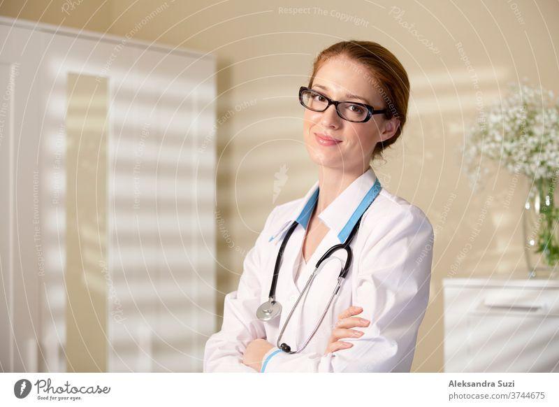 Junge schöne Ärztin im Unterricht und weißes Gewand mit Stethoskop, das ein großes Buch hält Pflege Karriere Kaukasier Klinik Mantel kompetent selbstbewusst