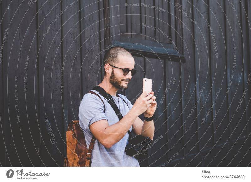 Ein Mann mit Sonnenbrille, Rucksack und professioneller Kamera fotografiert etwas mit einem Smartphone Tourist fotografieren Ausflug Reisender Fotograf lächeln