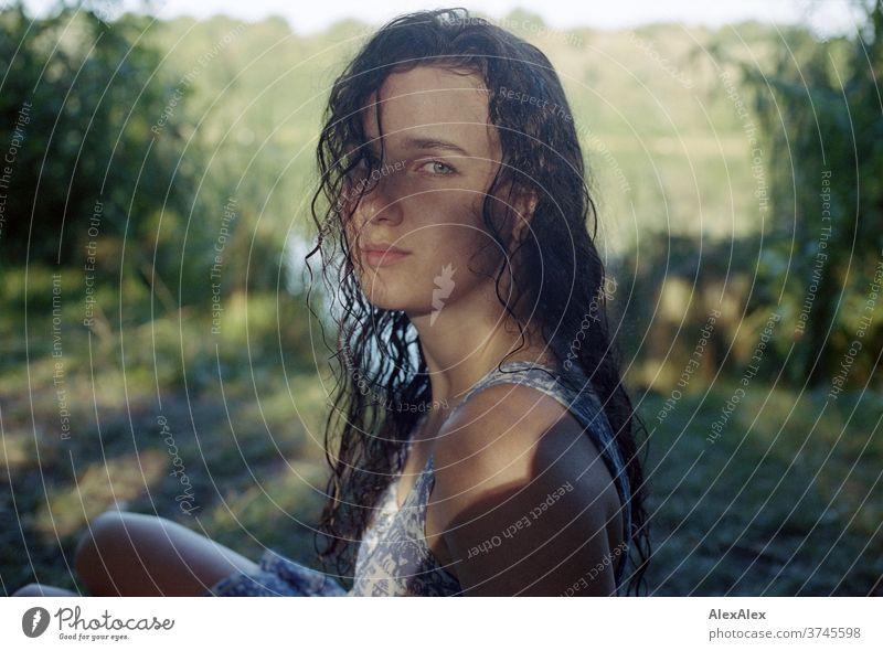 Analoges Portrait einer jungen Frau an einem Seeufer in der Natur mit Licht und Schatten durch Bäume schönes Wetter Stimmung selbstbewußt Kleid nasse haare