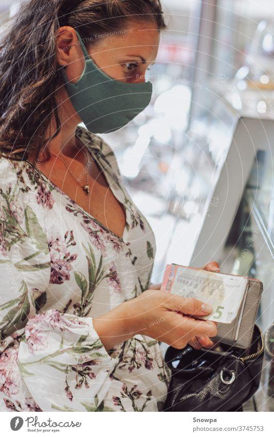 Junge Frau kauft Produkte mit Gesichtsmaske. Einkaufen während einer Pandemie. Reisen während einer Pandemie. Persönliche Sicherheit. sicheres Reisen reisen