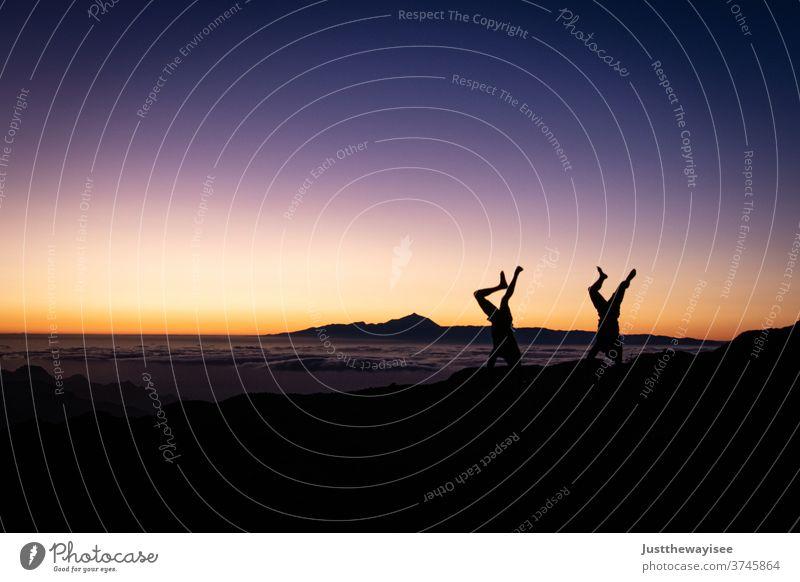 Silhouette von zwei Handständen mit dem Sonnenuntergang Himmel Gran Canaria Menschen Natur Berge u. Gebirge Landschaft orange Abenddämmerung Person Wolken Hügel