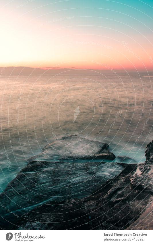 Ein rosaroter Sonnenaufgang im Frühling mit Blick auf den Ozean bei Bronte in Sydney, Australien. bronte Bäder Meer Pool pools nsw newsouthwales Ostküste Strand