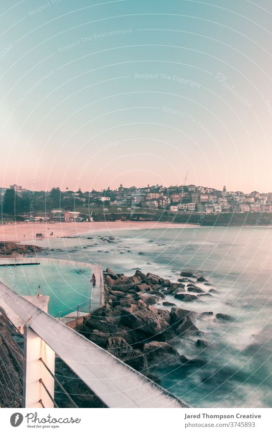 Ein rosaroter Sonnenaufgang im Frühling mit Blick auf die Bronte Baths in Sydney, Australien. bronte Bäder Meer Pool pools nsw newsouthwales Ostküste Strand