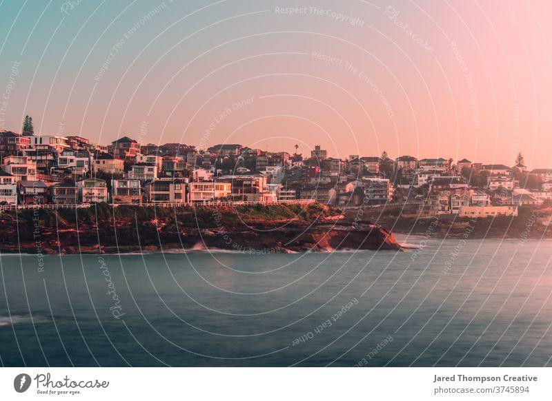 Ein rosaroter Sonnenaufgang im Frühling mit Blick auf Bronte und Tamarama in Sydney, Australien. bronte Bäder Meer Pool pools nsw newsouthwales Ostküste Strand