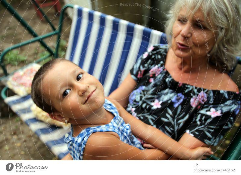 Oma hält lächelndes Kind, das in die Kamera schaut Porträt Liebe Liebkosen Wahrheit Vertrauen Lebensfreude Fröhlichkeit Gefühle Kindheit Paar