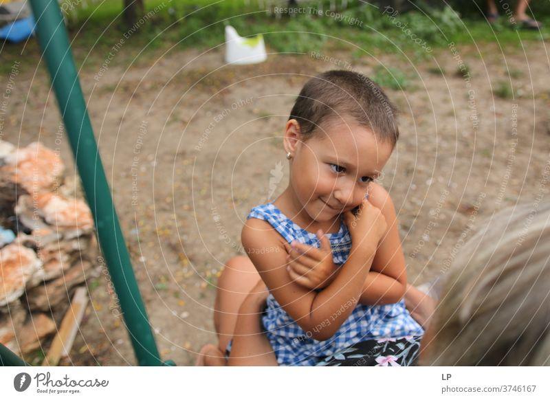 kleines Mädchen, das die Arme auf der Brust hält und einen Erwachsenen anschaut und anlächelt Arme hoch Schutz Körpersprache Mensch Gefühle Kommunizieren