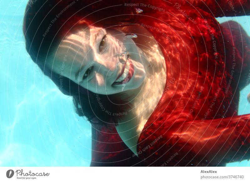 Unterwasser- Portrait einer jungen Frau in einem roten Kleid Mädchen junge Frau 18-25 Jahre schön sportlich Lächeln Lachen rothaarig dunkelhaarig fit tauchen