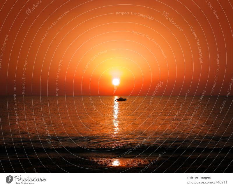 Sonnenaufgang Sonnenuntergang goldenes Sonnenlicht Meereshorizont mit Motorboot-Silhouette Küstenlinie Sonnenuntergang Meer Küstenlandschaft Sonnenstrahlen