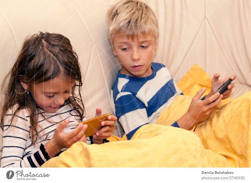 Kleines Mädchen und Junge spielen ein Spiel oder sehen sich etwas auf einem Smartphone an Cartoons Handy aussruhen Karikaturen anschauen Surfen im Netz