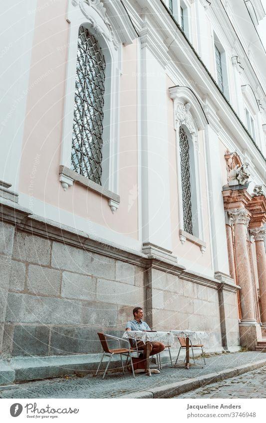 Mann sitzt in einem Straßencafe Café Kirche sitzen Erwachsene Außenaufnahme Tisch Kaffee Restaurant lässig Person trinken Straßencafé Getränk Tasse Lifestyle