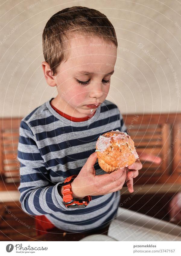 Junge genießt den süßen leckeren Muffin, den Sie selbst gebacken haben Kind Essen Cupcake Keks Dessert Glück essen Fröhlichkeit heiter klein wenig ungesund