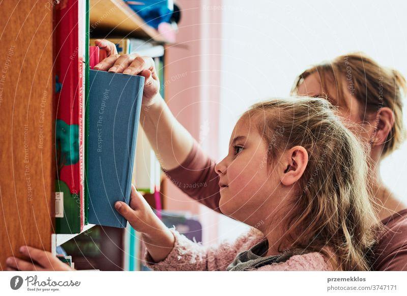 Kleines Mädchen im Vorschulalter wählt ein Buch zum Lesen Vorschulkind lesen auserwählend Bücherregal Bibliothek Bücherschrank Blick Bildung Fund Aussehen