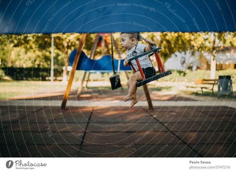 Kind spielt auf der Schaukel Kinderspiel Kindheit 0-12 Monate Spielen Spielplatz pendeln Freizeit & Hobby Kleinkind Tag Mensch Außenaufnahme Freude Farbfoto