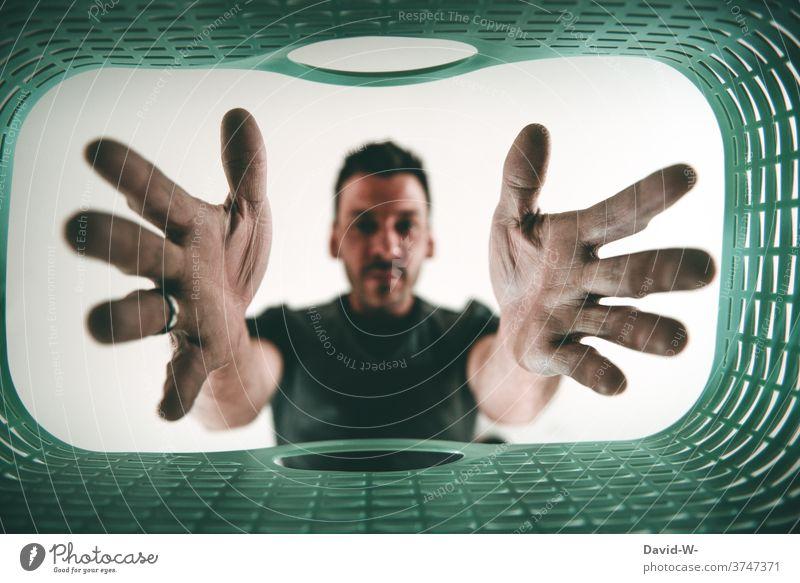 Mann greift in einen Wäschekorb Hausmann Haushalt Wäsche waschen aufräumen Haushaltsführung Waschtag genervt sauer Hände greifen