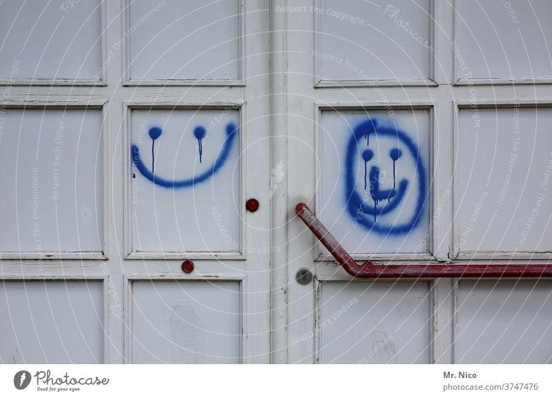 Smileys links und rechts Tür Eingang Eingangstür weiß blau Schmiererei Türgriff Lächeln Gute Laune geschlossen Griff Holztür alt Schloss Fröhlichkeit rund