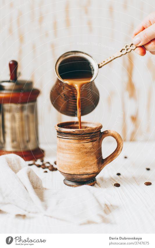 Kaffee in die Tasse giessen, Bohnen auf Holzuntergrund Aroma Frühstück hölzern Hintergrund Café Morgen trinken braun schwarz dunkel Getränk Koffein heiß frisch