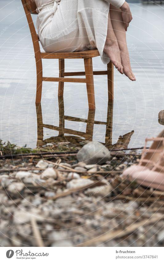 Frau sitzend auf Holzstuhl im Wasser Stuhl Sessel Sitzgelegenheit Möbel alt Einsamkeit braun Erholung ruhig warten Außenaufnahme Seeufer Steine Spiegelung Kleid