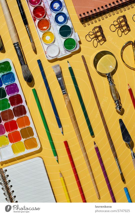 Flachlegung von Aquarellen, Pinseln, Notizbüchern und anderen Schreibwaren und Kunstgegenständen auf Gelb blanko Business farbenfroh kreativ Designer