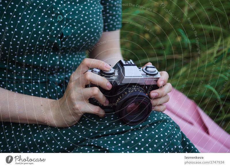 Nahaufnahme der Hände einer Frau, die eine alte Filmkamera halten Fotokamera Filmmaterial altehrwürdig Beteiligung gesichtslos Fotograf professionell Kleid