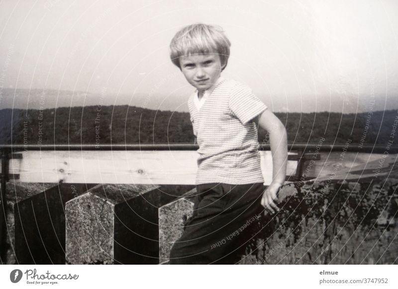 Erinnerungen an die 1970er Jahre - ein schwarz-weißer Fotoabzug zeigt ein Mädchen mit Bubikopf-Frisur und legerer Freizeitkleidung auf einem Turm stehend