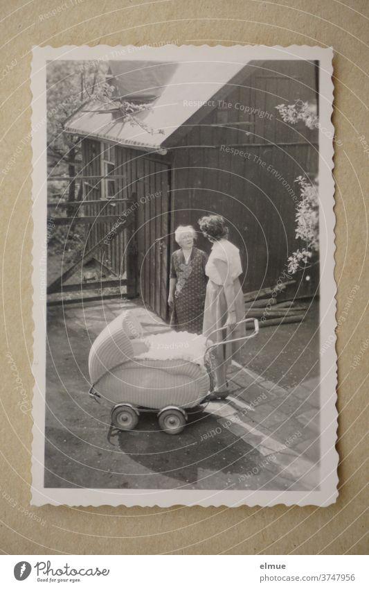 Erinnerungen an die 1960er Jahre - schwarz-weiß Bild mit Büttenrand zeigt drei Generationen in einem Vorgarten / modischer Kinderwagen und Mutter mit Großmutter im Gespräch