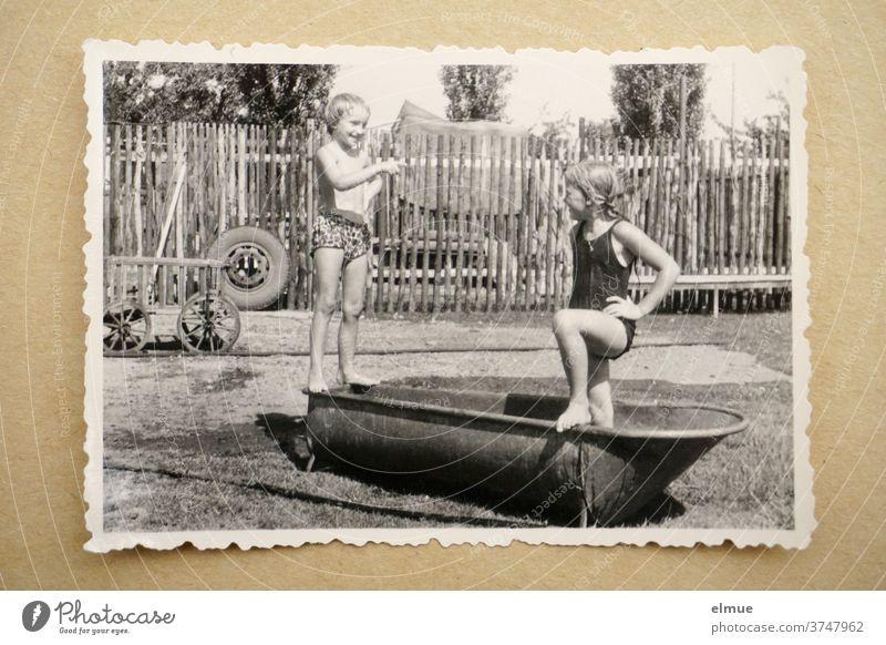Erinnerungen an die 1960er Jahre - ein schwarz-weißer Fotoabzug mit Büttenrand liegt auf beigefarbenem Papier und zeigt zwei Mädchen beim Baden in einer alten Zinkbadewanne in ländlicher Umgebung mit Zaun, Handwagen und Autoreifen