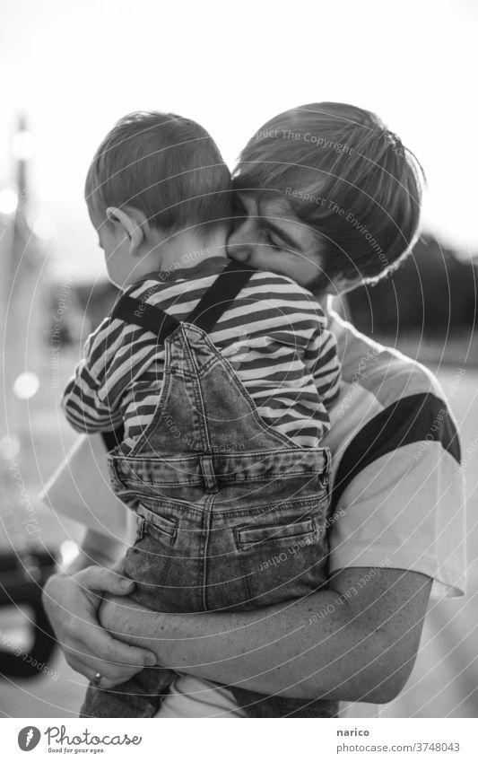 Vater hält Sohn liebend im Arm Kleinkind Junge Kind Außenaufnahme Kindheit 1-3 Jahre Natur Latzhose Leben Mensch Schwache Tiefenschärfe Schwarzweißfoto