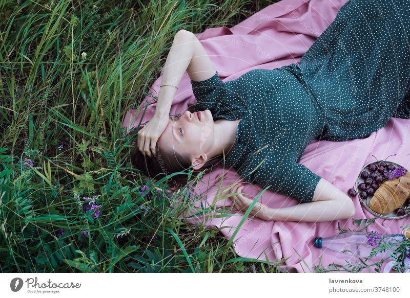 Porträt einer jungen erwachsenen Frau in grünem Kleid auf rosa Decke liegend mit Früchten, Gebäck und im Freien allein Kirsche Croissant Abend Gewebe