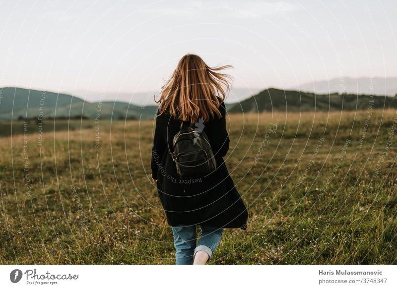 Frau mit Rucksack auf einem windigen Bergabenteuer Abenteuer weg von der Stadt Hintergrund schön Schönheit heiter Feld Freiheit Frischluft Spaß Gras Behaarung