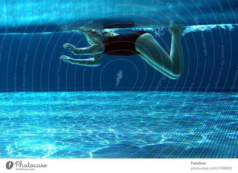 Schwimmen, schwimmen, schwimmen, einfach schwimmen, schwimmen, schwimmen... oder ein Mädchen, das im Pool schwimmt, den Kopf schön über Wasser haltend. blau