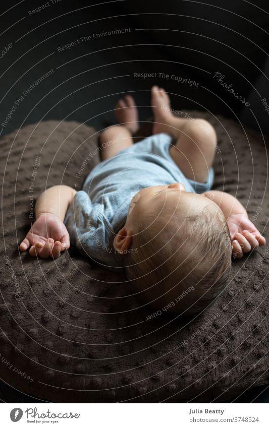 schlafendes Neugeborenes, das auf einem Kissen liegt und einen grauen Strampler trägt Säugling Baby Kind 0-12 Monate Kindheit klein niedlich entspannt offen