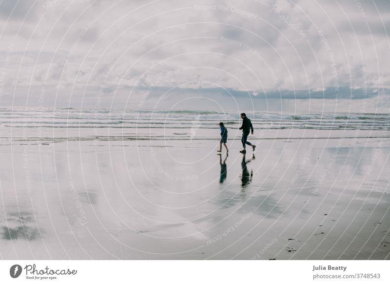 Vater und Sohn laufen als Silhouette am Strand von Oregon Reflexion & Spiegelung Betrachtungen Spiegelung im Wasser Nachdenken & Nachdenken Silhouetten