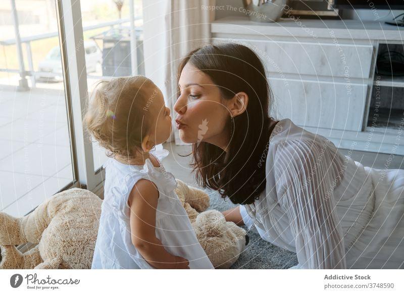 Frau liegt auf dem Boden und küsst ein Kleinkind zu Hause Kuss liebevoll Unschuld Zärtlichkeit anhänglich Kindererziehung Mama berührend Gefühl Säugling