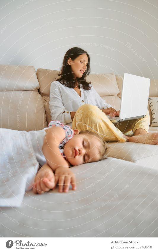Kleinkind schlafend, während ihre Mutter mit einem Laptop arbeitet Mutterschaft Zärtlichkeit Ruhe Sofa Verantwortung neugeboren Unschuld friedlich Drahtlos