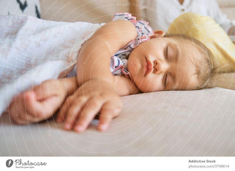 Kleines Mädchen liegt schlafend auf der Couch eines Hauses Zärtlichkeit Ruhe träumend neugeboren Unschuld Finger Frieden Kleinkind friedlich Kopfkissen bequem