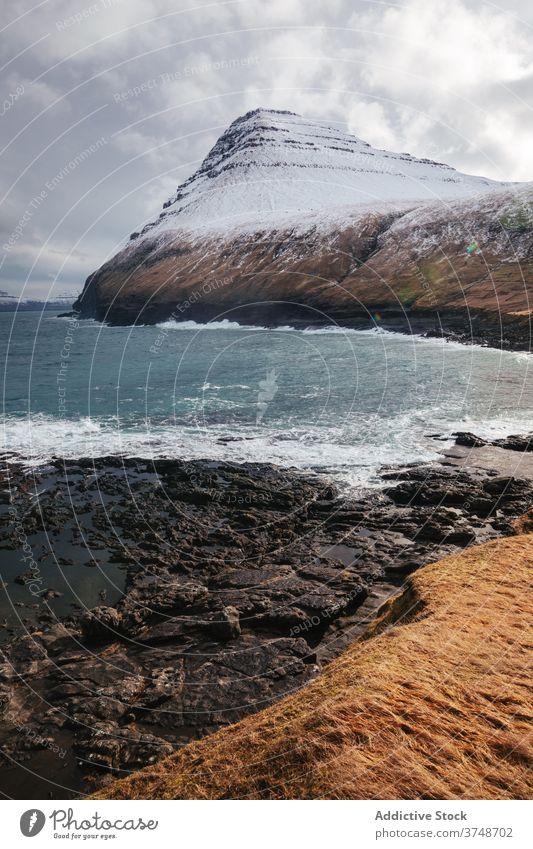 Felsenklippe in Meeresnähe auf den Färöer Inseln Klippe MEER Meereslandschaft Winter Schnee Saison kalt steil Gelände Färöer-Inseln felsig Landschaft