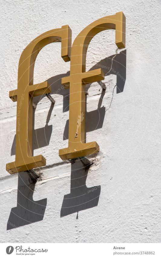 effeff Buchstabe Buchstaben F FF Gold golden Schatten Schrift Inschrift Überschrift kursiv schräg Relief Hauswand Shop Laden Ladenfront Druckschrift Serife