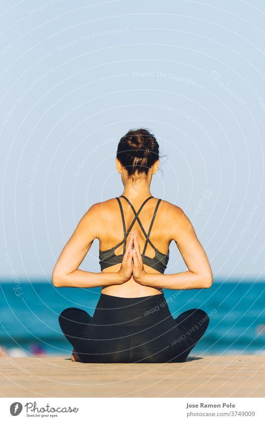 junge Frau von hinten, die an einem sonnigen Tag vor dem Meer Yoga macht Rücken Meditation Gesundheit Sand Sitzen Menschen passen Erholung Sonnenschein ruhig